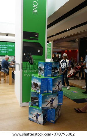 SAN FRANCISCO - OCTOBER 11:  Kid in football gear plays Madden Xbox One as people watch inside Microsoft Windows Store who's technology is in most modern computers, San Francisco October 11, 2015. - stock photo