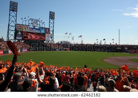 SAN FRANCISCO - OCTOBER 2: Padres vs. Giants: Fans wave orange towels to pump up team before the start of the game as the big screen tells to do.  October 2 2010 Att Park San Francisco California. - stock photo