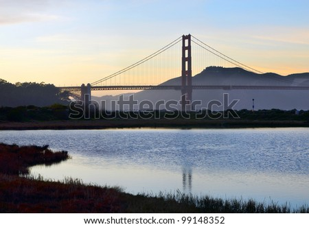 San Francisco's Golden Gate Bridge reflected in the wetlands at Crissy Field at dusk - stock photo