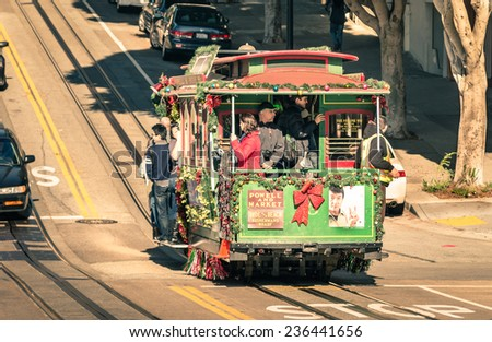 SAN FRANCISCO, UNITED STATES - DECEMBER 15, 2013: people riding a Powell Hyde cable car at Hyde Street. With twenty-three lines, the city cable system is the world's last manually operated service.   - stock photo