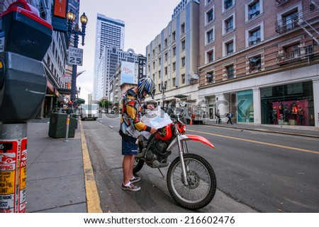 SAN FRANCISCO, USA - OCT 4, 2011: Young motorcyclist checking directions on map at city street on Oct 4, 2011 in San Francisco, USA  - stock photo