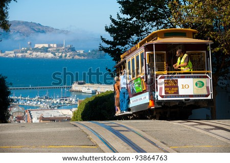 SAN FRANCISCO, USA - SEPT. 21: A cable car, iconic San Francisco transportation, meets Alcatraz Prison at the top of Hyde Street  September 21, 2011 in San Francisco, California, USA - stock photo