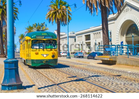 San Francisco vintage f- streetcar, train, tram or muni cable trolley car traveling down the Embarcadero on a sunny day.  Originally a Minneapolis car built in 1947 trolley No 1071   Tribute livery. - stock photo