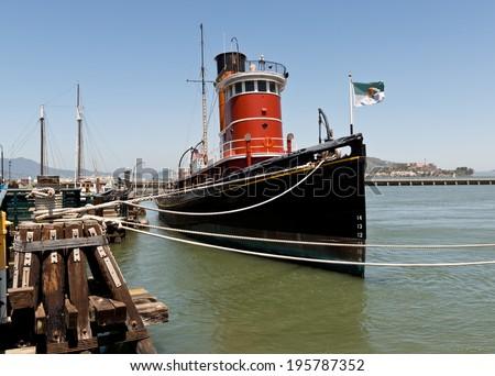 San Francisco Vintage Tug Boat and Alcatraz Island - stock photo