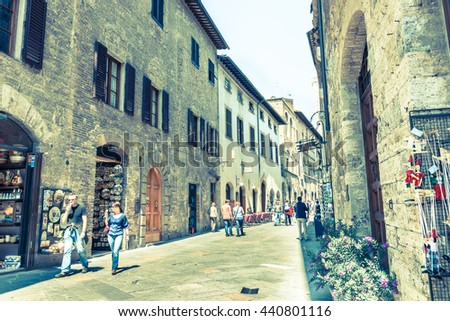 SAN GIMIGNANO, ITALY - APRIL 18; Old image faded colors effect of tourists in in narrow street Italian  Tuscan walled city on April 18, 2011 San Gimignano, Italy