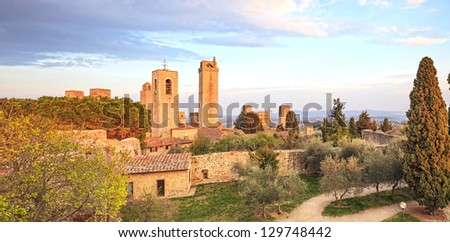 San Gimignano landmark medieval town. Sunset on towers and park with cypress and olive trees. Tuscany, Italy, Europe. - stock photo