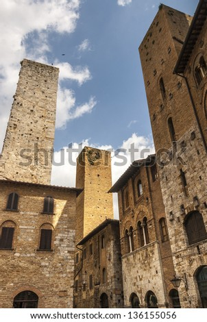 San Gimignano (Siena, Tuscany, Italy) - Street with ancient buildings and two towers - stock photo