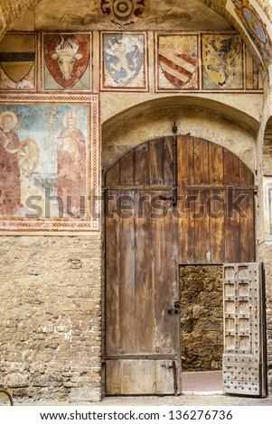 San Gimignano (Siena, Tuscany, Italy) - Wooden door of medieval palace, with frescos - stock photo