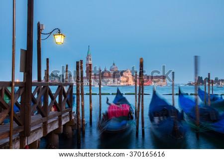 San Giorgio island and gondolas floating in the Grand Canal at night, Venice, Italy - stock photo