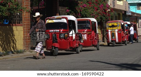 SAN JUAN LA LAGUNA, GUATEMALA -  NOVEMBER 27: a man goes to the market, wearing hat and traditional trousers, near some red tuk-tuks , on November 27, 2013, in San Juan La Laguna, Guatemala.  - stock photo