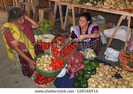 SAN JUAN LA LAGUNA, GUATEMALA -  NOVEMBER 27: Two Indian women, wearing the traditional indigenous clothes,at the market of the town center,  on November 27, 2013, in San Juan La Laguna, Guatemala.  - stock photo
