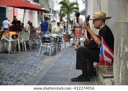 SAN JUAN, PUERTO RICO - MARCH 20:  A street performer serenades visitors for tips in Old San Juan on March 20, 2016.  Tourism revenue has remained relatively unaffected by the island's budget crisis. - stock photo
