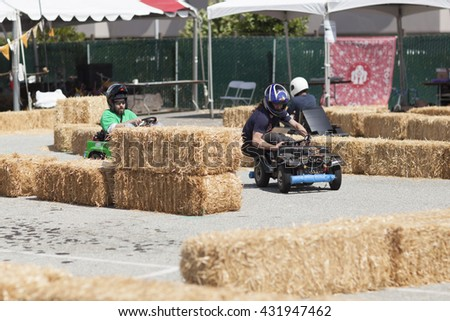SAN MATEO, CA May 20 2016 - A driver looks ahead around a curve during a power wheels race at the 11th Annual Bay Area Maker Faire at the San Mateo County Event Center.