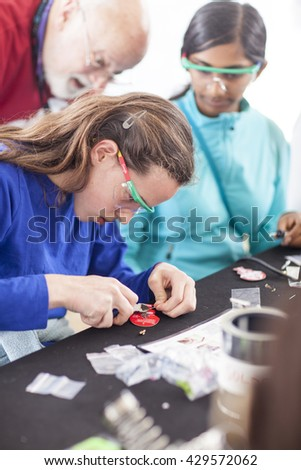 SAN MATEO, CA May 20 2016 - A girl working on electronics at the 'Learn to Solder' activity station presented by Google at the 11th Annual Bay Area Maker Faire at the San Mateo County Event Center.