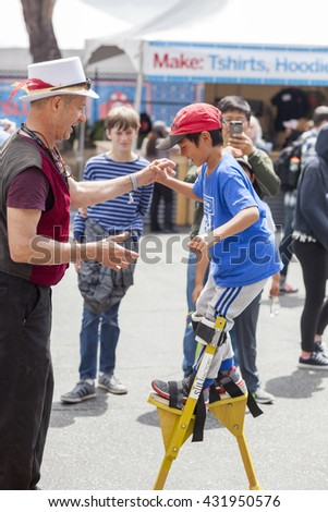 SAN MATEO, CA May 20 2016 - A young child receives stilt lessons during the 11th annual Bay Area Maker Faire at the San Mateo County Event Center. - stock photo