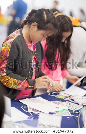 SAN MATEO, CA May 20 2016 - A young girl works on a project during the 11th Annual Bay Area Maker Faire at the San Mateo County Event Center. - stock photo