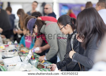 SAN MATEO, CA May 20 2016 - Attendees at a crafting booth during the 11th annual Bay Area Maker Faire at the San Mateo County Event Center. - stock photo
