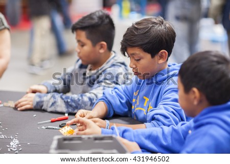 SAN MATEO, CA May 20 2016 - Children work during a free build activity at the 11th annual Bay Area Maker Faire at the San Mateo County Event Center. - stock photo