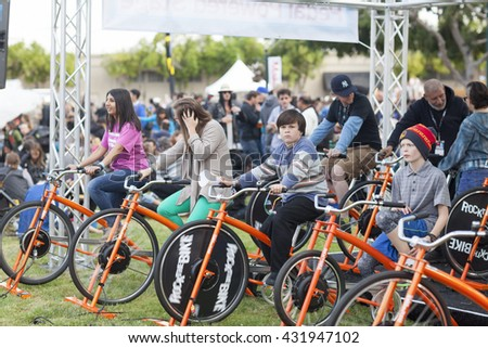 SAN MATEO, CA May 20 2016 - Members of the audience pedal stationary bicycles to power a musical performance during the 11th annual Bay Area Maker Faire at the San Mateo County Event Center. - stock photo