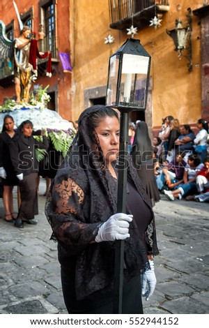 SAN MIGUEL DE ALLENDE, MEXICO - APRIL 6, 2007: Woman wearing a black lace shawl carries a candle torch in the Holy Week procession on Good Friday. The 4-mile pageant attracts thousands of spectators.