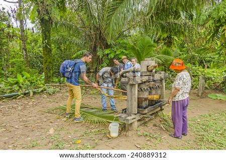 SAN MIGUEL DEL BALA, BOLIVIA, MAY 11, 2014: Tourists produce sugar cane juice in wooden press at the indigenous community while local people help them to do it - stock photo