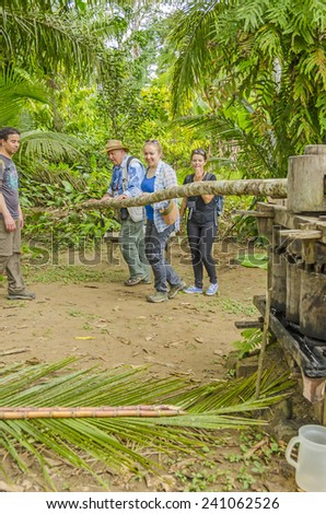 SAN MIGUEL DEL BALA, BOLIVIA, MAY 11, 2014: Tourists produce sugar cane juice in wooden press at the indigenous community in Bolivian jungle - stock photo