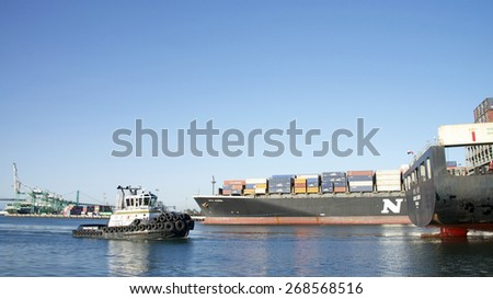 SAN PEDRO, CA - APRIL 09, 2015: Tractor Tugboat TIM QUIGG off the stern of Cargo Ship HANJIN XIAMEN. Tugboats are vital for safe, efficient entry and exit for the large ships.