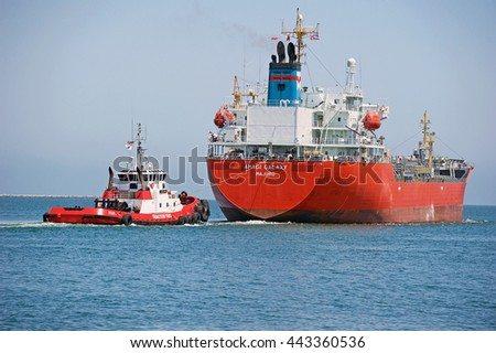SAN PEDRO/CALIFORNIA - JUNE 22, 2016: Amagi Galaxy an oil / chemical tanker ship being escorted out of the channel by a tractor tug boat at the Los Angeles Harbor, in Los Angeles, California USA