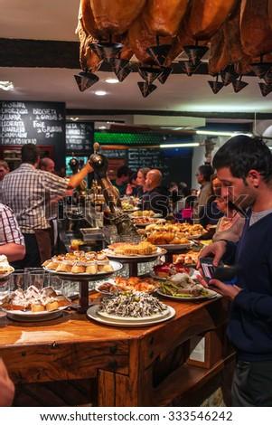 SAN SEBASTIAN, SPAIN - SEPTEMBER 28, 2014: View of a bar with traditional pinchos in San Sebastian, Basque Country, Spain. Pinchos (Pintxos) are traditional appetizer in Basque country. - stock photo