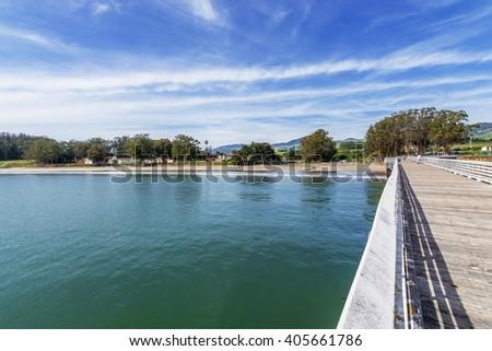 San Simeon Bay, Pier & W R Hearst Memorial State Beach, blue sea & sky, people on the beach & pier, located on the rugged Big Sur coastline, near Cambria, CA. on the California Central Coast. - stock photo