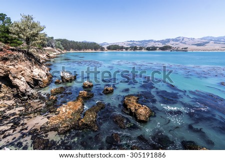 San Simeon Bay, Pier & W R Hearst Memorial State Beach, people on the beach, and kayaking in the water, located on the rugged Big Sur coastline, near Cambria, CA. on the California Central Coast. - stock photo