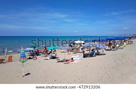 SAN VINCENZO, ITALY - JULY 31, 2016: Mediterranean beach with people lying on the sand and swimming in the sea. Space at the top and bottom for copy.