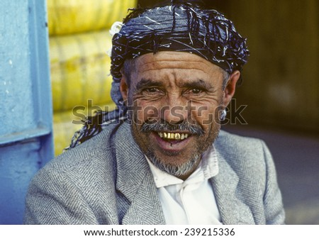 SANAA, YEMEN - JUNE 30, 1991: portrait of old smiling man in Sanaa, Yemen. The man wears gold teeth which are a symbol for wealth and rich people,
