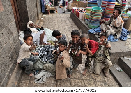 SANAA, YEMEN - MARCH 22, 2012: Children playing with toy guns on the street of Sanaa - stock photo