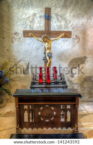 Sanctuary at Mission Concepcion featuring an altar, crucifix, wall engravings, and drawings - stock photo