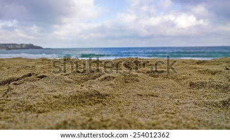 Sand and sea on a beach in Cornwall  on a overcast day during the winter