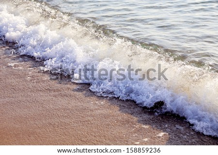 Sand and wave in sunny day. Whole background - stock photo