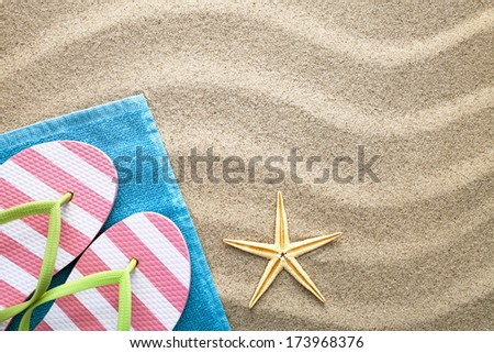 Sand background with towel, flip flops and starfish. Summer concept. Top view  - stock photo