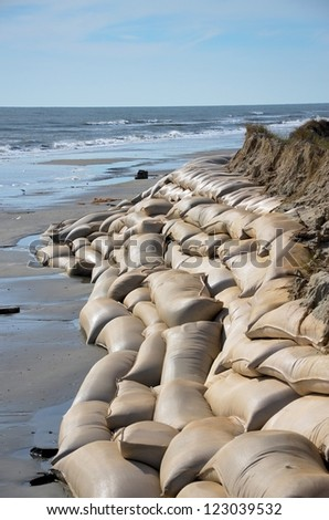 Sand bags along the beach in North Carolina to protect from heavy surf and erosion. - stock photo