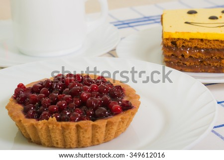 Sand basket with cranberries on white plate and honey cake - stock photo