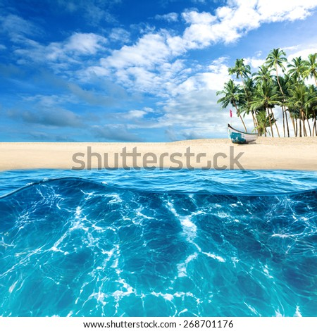Sand beach on tropical island. View from sea water - stock photo