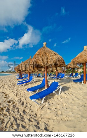 Sand beach with some grass umbrellas at the luxury caribbean resort. Vertical.