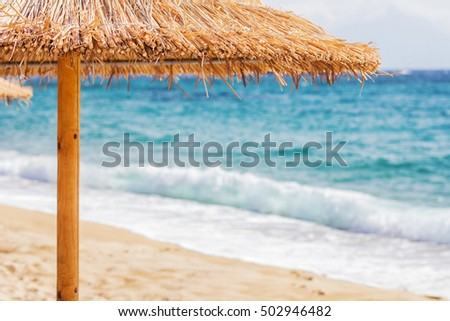 Sand beach with straw sunshades ,beautiful colors of the sea,summer travel vacation.