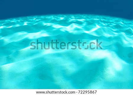 sand bottom with sun reflections - stock photo