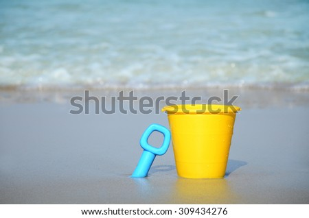 sand bucket and shovel in the sand by the water - stock photo