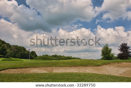sand bunker before reaching the hole, vibrant sky