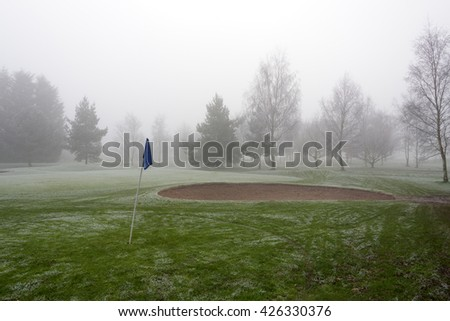 Sand bunker on an empty golf course on a cold and foggy day - stock photo