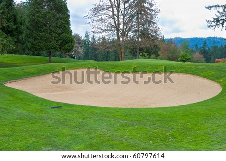 Sand bunker on the golf course with green grass and trees. - stock photo