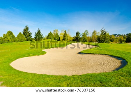 Sand bunker on the golf course with green grass and trees over blue sky. - stock photo