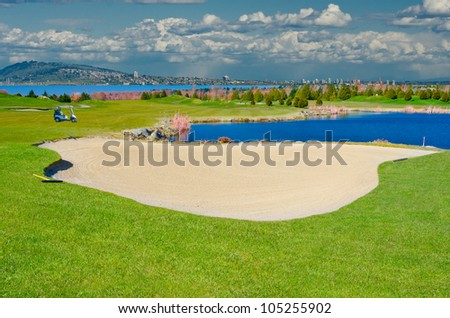 Sand bunker on the golf course with the pond and urban background . - stock photo